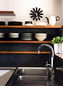 Kitchen shelves on dark grey tiled wall next to stainless steel sink
