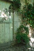Wrought iron chandelier in front of wooden door of farm house and chair covered with climbing plants