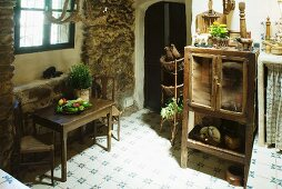 Simple kitchen table and chairs below window and old kitchen cupboard in dining room of farm house