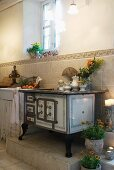 Vintage kitchen stove on platform against half-height wall tiling in simple, country house kitchen