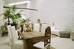 Rustic wooden table and chairs with white covers in Mediterranean loggia