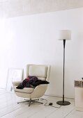 Stack of clothes on comfortable, leather swivel chair and standard lamp in informal artist's apartment with white furnishings and surfaces
