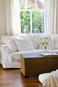 White sofa and wicker table in front of window