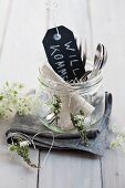 Welcome sign and cutlery in preserving jar next to hearts made from wire and herbs