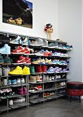 Collection of trainers in open, metal shoe rack next to small, retro upholstered stool