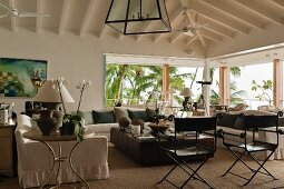 A large living area with a view of palm trees under a sloping roof