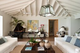 A living room with white upholstered furniture, a solid wooden coffee table and a open grand piano
