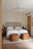 Twin beds with tall, upholstered headboards and two large wicker trunks at foot
