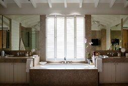 Marble bathtub below half-closed window shutters in spacious bathroom