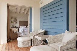 Comfortable balcony furniture with footstool and tray table against blue wall and view into bedroom through open sliding door