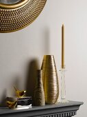 Vases and candlesticks on shelf below mirror