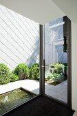 Blick durch Fensterfront in Innenhof mit Pflanzenstreifen vor Hauswand