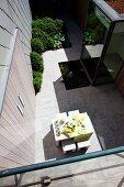 Blick von oben auf gedeckten Tisch auf sonnenbeschienener Terrasse im Innenhof eines zeitgenössischen Wohnhauses