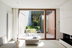 Blick von Designer Wohnzimmer durch Terrassenfenster auf Outdoormöbel in patioartigem Innenhof