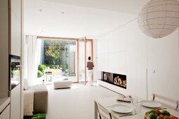 Gedeckter Esstisch in Designer Wohnzimmer mit Blick durch raumhohes Fenster auf Terrasse