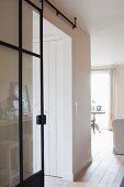 Gläserne Schiebetür mit schwarzem Metallrahmen in weißem Raum mit hellen Holzdielen