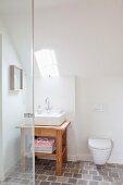 Wandtoilette unter der Dachschräge mit kleinem Lichtfenster und darunter stehendem Holzwaschtisch mit rechteckigem Waschbecken