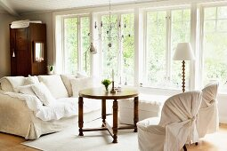 Sofa set with white covers in front of window in living room
