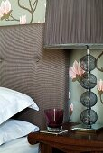 Coloured drinking glass next to table lamp with fabric shade on bedside table next to bed with upholstered headboard