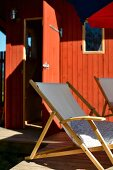 Deckchairs on terrace in front of wooden house painted rust red