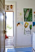 View through door into simple kitchen with posters on wall next to doorway and view of outdoors