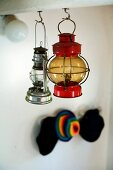 Different vintage paraffin lamps hanging from hooks in underside of wooden beams