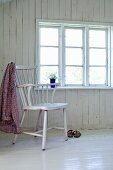 Shirt hung over back of chair in plain room with white-painted wooden floor