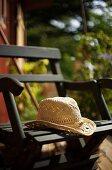 Straw hat on wooden garden chair