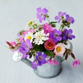 Posy of garden flowers in metal watering can