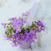 Purple flowers (cranesbill) and handwritten card in pot on vintage wooden surface