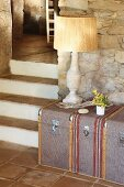 Traditional table lamp on steamer trunk against stone wall next to terracotta-tiled steps