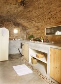 Bathroom with stone walls, wooden cupboard doors in concrete washstand and concrete floor with pebble border