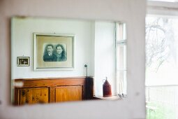 Old, framed photos hanging above wood panelling in farmhouse
