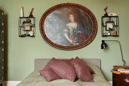 Traditional portrait of woman and wall racks of memorabilia above French bed