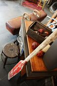 Unusual furnishings and old sporting equipment; dried pomegranates in rusty container
