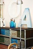 Old ornamental letters and blue soda siphons on vintage metal shelves with wooden top