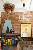 Enormous letter A leaning against brick wall behind Eames chair and pommel horse