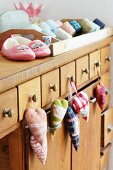 Shop counter with scented sachets hanging from handles; slippers, toiletry bags and rolls of ribbon on counter