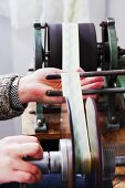 Fabric ribbon being wound onto spool by machine