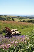 Rattan sun loungers in meadow with view across French landscape