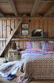 Bedroom with double bed in wooden cabin
