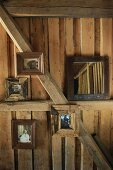 Photos with wooden frames on wall and wooden beams of cabin