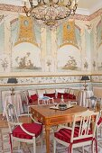 Chairs painted pale grey with red seat cushions around antique table in grand salon with murals on walls