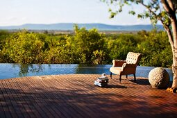 Infinity pool with broad wooden deck looking out over wide landscape