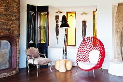 Ethnic artworks and designer chairs next to fireplace in rustic brick wall