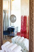 Rolled towels against bathroom mirror with designer chairs and lamps reflected in background