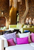 Modern seating ensemble within rustic brick walls with tree trunk as roof support