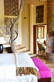 Foot of staircase with integrated, rustic tree trunk; modern African artworks on walls