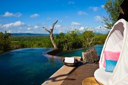 White, circular lounger with canopy in front of boundless sky and blue infinity pool