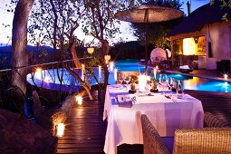 Infinity pool with underwater lighting at twilight; table set with white cloth for candlelight dinner in foreground
